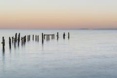 光滑的海和码头废墟的平安的概念风景图象 免版税库存图片