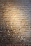 光轻的补丁在老涂灰泥的砖墙上的 库存图片