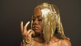 光滑的非裔美国人的妇女特写镜头超现实的画象有明亮的金黄构成和Headwear的 古铜身体画图 股票视频