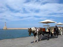 克利特希腊登陆了持续的飞机光芒星期日 威尼斯式灯塔和马与推车在干尼亚州镇 免版税库存图片