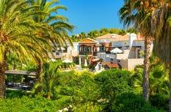 克利特海岛,希腊, 2011年7月01日:在旅馆别墅的看法游人客人的 绿色热带棕榈树游泳池,太阳床, 库存照片