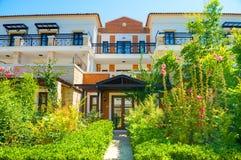 克利特海岛,希腊, 2011年7月01日:在旅馆豪华vip别墅的看法游人客人的 绿色热带树旅馆庭院 选件类 库存图片