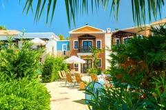 克利特海岛,希腊, 2011年7月01日:在皇家母马村庄旅馆别墅沙滩伞海滩睡椅的看法游人客人的 希腊语 免版税库存图片
