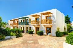 克利特海岛,希腊, 2011年7月01日:在Aldemar旅馆别墅的看法在游人客人的五颜六色的花中 古典希腊语旅馆 免版税图库摄影