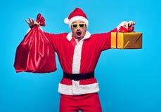 克劳斯・圣诞老人 愉快的圣诞老人年轻人 大袋袋子礼物 免版税库存照片