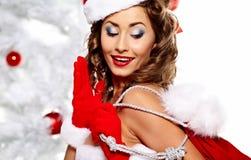 克劳斯给女孩针佩带的圣诞老人穿衣  图库摄影