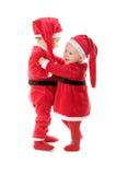 克劳斯给婴儿圣诞老人穿衣 库存照片