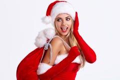 克劳斯给女孩圣诞老人性感佩带穿衣 图库摄影