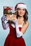 克劳斯给礼品女孩圣诞老人穿衣 免版税库存照片
