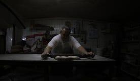 贝克在古色古香的面包店工厂和商店的工作 库存照片
