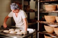 贝克在面包的面团做手工切开 面包制造  烘烤 免版税库存图片
