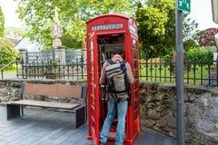克尼格斯温特尔,德国- 2019年5月23日 自由图书交换的一个红色电话亭 看在电话的一个人一本书 库存照片