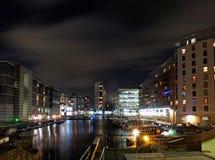 克拉伦斯镇船坞利兹在与被停泊的驳船和被月光照亮云彩的晚上在反映的明亮地有启发性海滨大厦 免版税库存照片