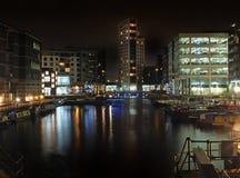克拉伦斯镇船坞在利兹在与在水和小船反映的明亮地有启发性大厦的晚上被停泊沿边 库存照片