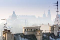 克拉科夫及时圣诞节打过工,在多雪的屋顶的鸟瞰图在城市的中央部分 Wawel城堡和大教堂 波兰 欧洲 免版税库存照片