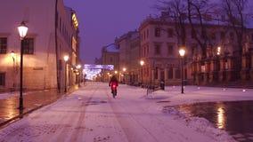 克拉科夫老镇街道和偏僻的骑自行车的人骑马在雪 免版税库存照片