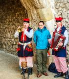 克拉科夫,波兰- 2017年11月19日:从亚洲的愉快的游人拍摄与传统波兰衣裳的地道音乐家 免版税库存照片