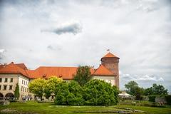 克拉科夫,波兰- 2017年6月04日:在多云天空的Wawel城堡 与绿色树和草草坪的设防大厦 建筑学a 免版税库存图片