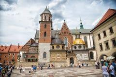 克拉科夫,波兰- 2017年6月04日:有教堂的Wawel大教堂多云天空的 方形的infront天主教会的人游人 杨梅 图库摄影