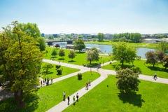 克拉科夫,波兰- 2016年6月08日:走沿维斯瓦河的人们在Wawel历史复合体在克拉科夫, 2016年6月附近开户08日- 免版税库存图片