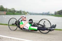 克拉科夫,波兰- 4月28 :Cracovia Marathon.Handicapped人在一个轮椅的马拉松运动员在城市街道上 免版税图库摄影