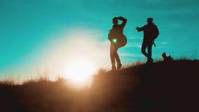 克服困难胜利成功的配合 有背包的两个游人剪影徒步旅行者人在日落去步行 影视素材