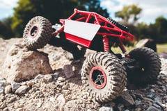 克服岩石特写镜头的玩具履带牵引装置 免版税库存图片