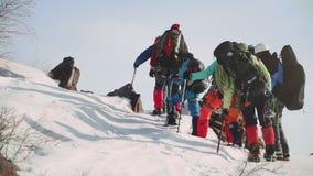 克服疲劳每小组登山人登高对积雪覆盖的山,与在鞋子和滑雪杆的钉 股票视频