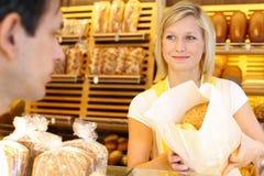 贝克的商店店主给面包顾客 库存图片