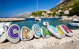 克罗地亚在石头绘的国名,小船在背景中 免版税库存照片