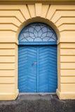 克里斯蒂安桑挪威, 2017年10月22日:在黄色修造的Tollboden的老蓝色木门在克里斯蒂安桑 免版税库存照片