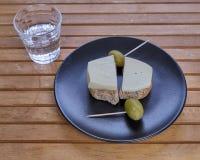 克里特岛面包干用地方瑞士格里尔干奶酪、橄榄和raki玻璃  免版税库存图片