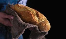 贝克` s手拿着在黑暗的背景的新鲜面包 库存图片