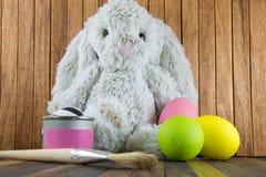 兔子兔宝宝和复活节彩蛋和瓶子桃红色油漆 库存图片