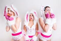 兔子服装的三个女孩吃红萝卜的 免版税库存照片