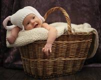 兔子服装的微笑的婴孩在篮子 免版税库存照片