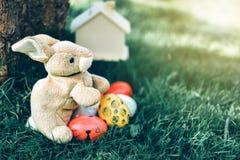 兔子玩偶用在绿草的复活节彩蛋在庭院里 库存图片