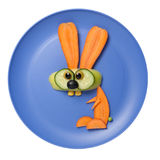 兔子由未加工的蔬菜做成在蓝色板材 库存图片