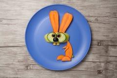 兔子由红萝卜制成在板材和桌 免版税库存图片
