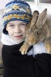兔子肩膀的男孩举行。 库存图片