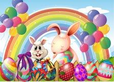 兔宝宝和五颜六色的鸡蛋在彩虹和浮动气球附近 免版税库存照片