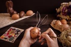 兔宝宝复活节 绘在木桌上的女性手复活节彩蛋 免版税库存图片