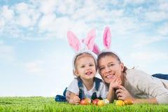 兔宝宝复活节 有作为复活节bunn打扮的母亲的小女孩 图库摄影