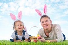 兔宝宝复活节 有作为复活节bunn打扮的母亲的小女孩 免版税库存照片