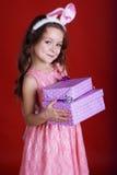 兔宝宝女孩拿着礼物盒 免版税库存图片
