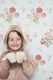 兔宝宝服装的逗人喜爱的女孩反对墙纸 库存图片