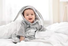 兔宝宝服装的逗人喜爱的矮小的婴孩在家坐床 免版税库存图片