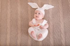 兔宝宝服装的逗人喜爱的矮小的婴孩有红萝卜说谎的 免版税库存图片