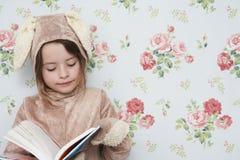 兔宝宝服装读书的女孩反对墙纸 免版税库存照片