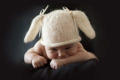 兔宝宝盖帽的逗人喜爱的新出生的婴孩 免版税库存照片